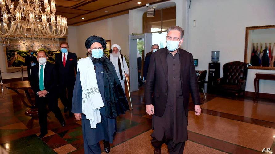 Pakistan's Foreign Minister Shah Mahmood Qureshi, right, and Mullah Abdul Ghani Baradar