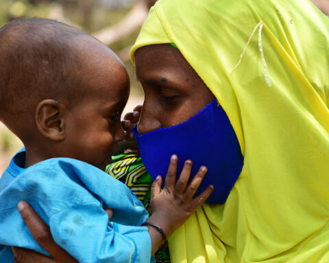 A baby plays with her mother's mask