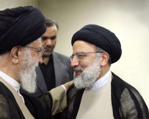 Iranian Supreme Leader Ayatollah Ali Khamenei (left) talks to Ebrahim Raisi