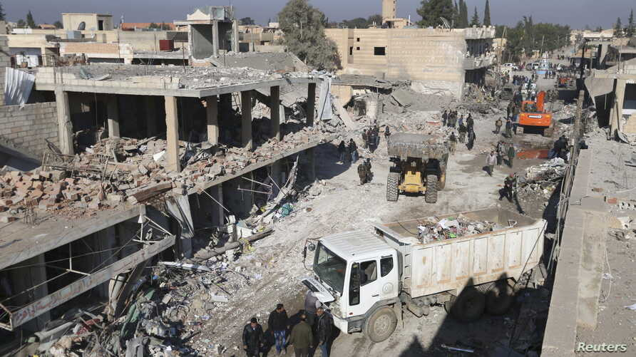 Residents inspect damage at a site hit by one of three explosive trucks, in the YPG-controlled town of Tel Tamer, Syria